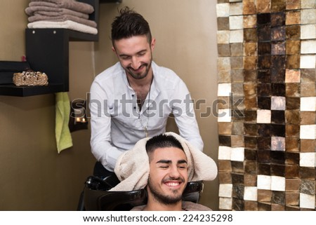Hairstylist Hairdresser Washing Customer Hair - Young Man Relaxing In Hairdressing Beauty Salon - stock photo