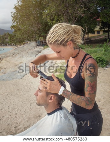 Hairstylist making men's haircut at the sand beach