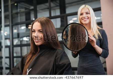 Hairstylist making women's haircut to an attractive woman in the beauty salon