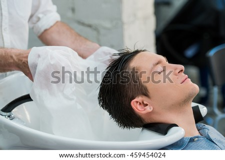 Hairstylist washing client's hair in barber shop