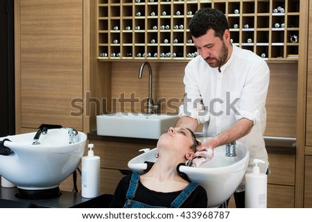 Hairstylist washing head to the young woman at the hairdresser