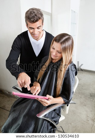 Hairstylist with female client using digital tablet at parlor