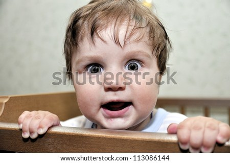 Hairy baby leans on bed and smiles - stock photo