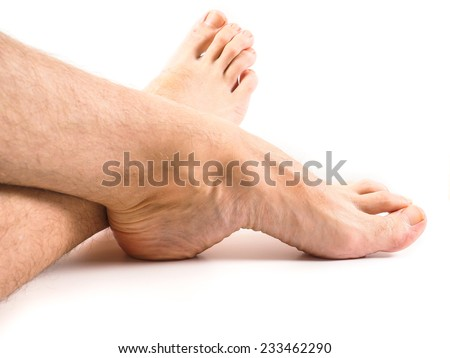 Hairy legs and feet of male person resting towards white background - stock photo