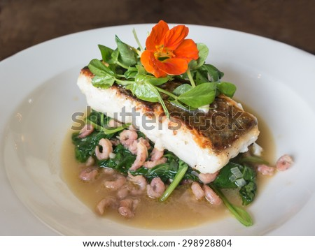 Hake prepared with spinach and shrimps and garnished with watercress and an orange flower.
