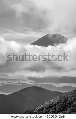 Hakone, Japan - September 27, 2016: Black and white portrait of the summit of mount Fuji visible and encircled by bands of clouds as it is seen from Mount Komagatake. Valley in foreground.