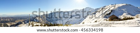 Hakuba mountain range on a clear sunny day. The very steep mountain area is between two ski resorts, Happo-One and Goryu. A natural flat area between the ranges is inhabited by the local villagers. - stock photo