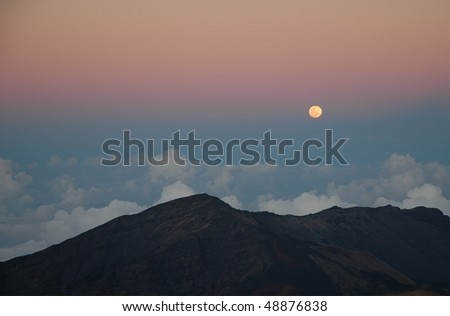 Haleakala National Park at 10,000 feet in elevation. Full moon at night shinning down on the top of the clouds