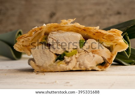 Half a chicken and leek pie on a wooden surface with fresh leeks in the background. - stock photo