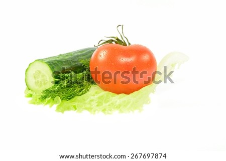 Half a cucumber, a tomato, dill on a piece of lettuce on a white background - stock photo