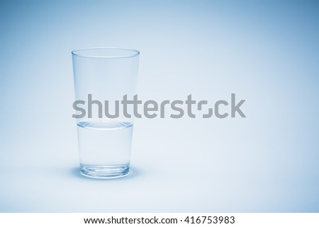 Half a glass of water with blue background.