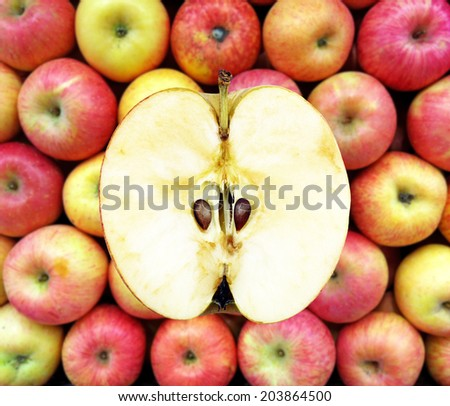 Half an apple against a basket of red apple.  - stock photo