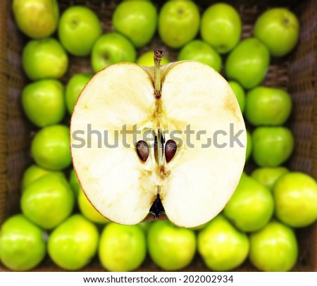 Half an apple fruit against a basket of green apple.  - stock photo