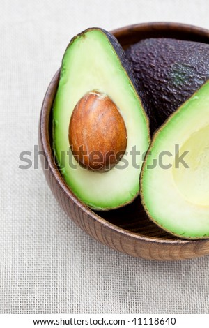 Half an avocado in an old wooden bowl - stock photo