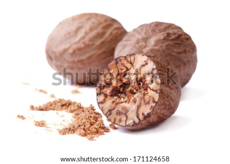 half and whole nutmegs isolated on a white background closeup - stock photo