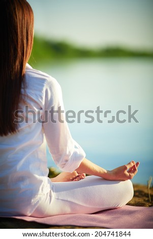 Half back of meditating woman relaxing in pose of lotus outdoors - stock photo