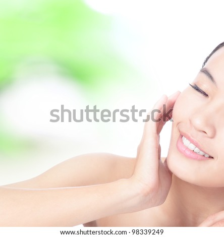 Half beautiful woman Face and hand touch face with smile on green background, model is a asian beauty