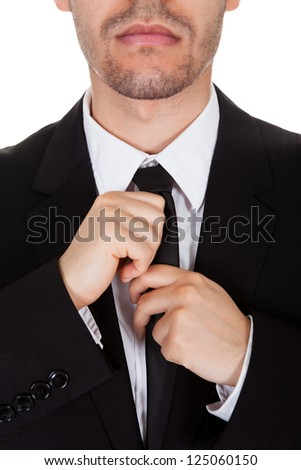 Half body portrait of a handsome young businessman standing straightening his tie isolated on white - stock photo