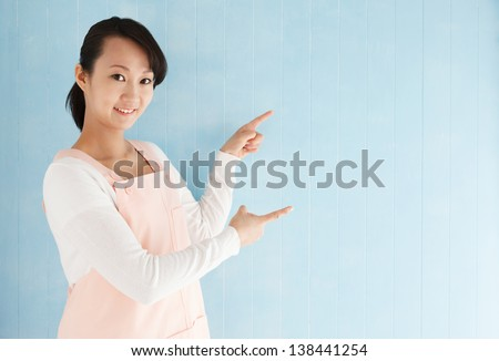 Half body portrait of beautiful young japanese woman wearing an apron pointing with blue tiled background and copy space. - stock photo