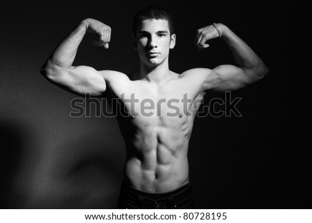 Half body portrait of muscular young man, black and white studio background. - stock photo