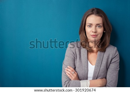 Half Body Shot of a Confident Young Office Woman Looking at the Camera Against Plain Blue Green Wall with Copy Space - stock photo