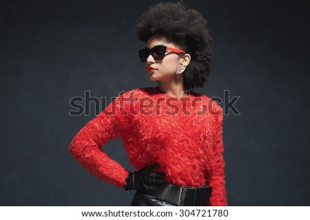 Half Body Shot of a Fashionable Pretty Young Woman in Fuzzy Long Sleeved Shirt with Sunglasses Looking Into the Distance. - stock photo
