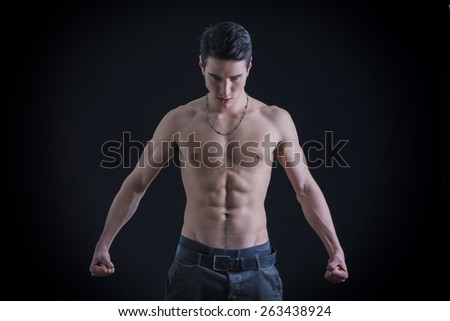 Half Body Shot of a Handsome Topless Muscular Man Clenching his Fists Down on his Both Sides While Looking at the Camera Fiercely. Isolated on Black. - stock photo
