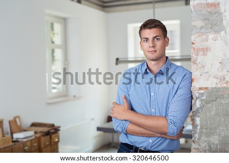 Half Body Shot of a Handsome Young Businessman Leaning Against Wall with Arms Crossing on his Chest and Looking at the Camera. - stock photo