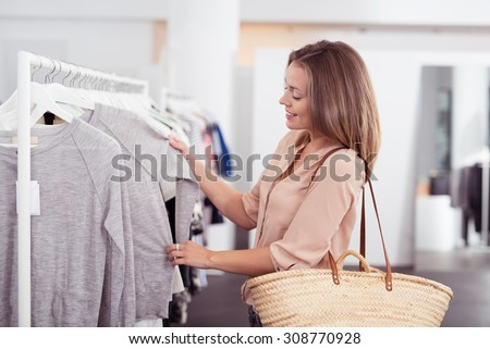 Half Body Shot of a Happy Young Woman with Shoulder Bag Looking at Clothes Hanging on the Rail Inside the Clothing Shop. - stock photo