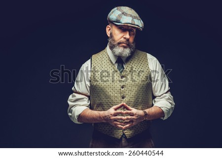 Half Body Shot of a Middle Age Man in a Trendy Green Outfit with Ivy Cap, Posing on Black Background with Hands In front his Belly While Looking at the Camera Seriously. - stock photo