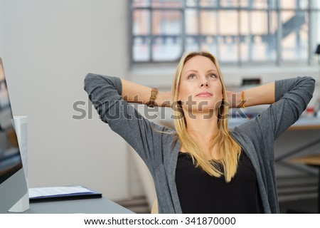 Half Body Shot of a Pensive Office Woman Looking Up with Hands Behind her Head While Relaxing at her Desk. - stock photo