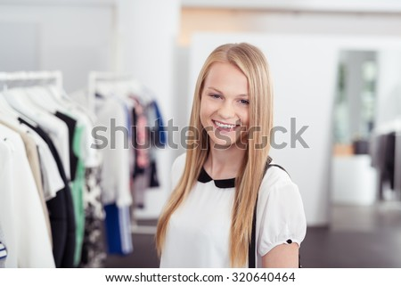 Half Body Shot of a Pretty Blond Girl Smiling at the Camera Inside the Clothing Store. - stock photo
