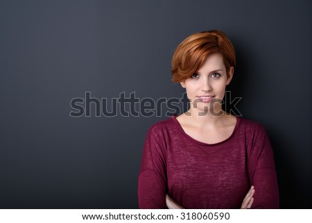 Half Body Shot of a Pretty Woman in Maroon Shirt Smiling at the Camera Against Gray Wall Background with Copy Space.
