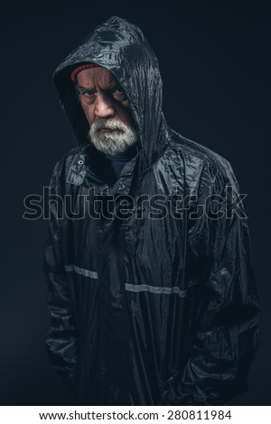 Half Body Shot of a Serious Bearded Senior Man Wearing Black Raincoat, Staring at the Camera. Isolated on Black Background. - stock photo
