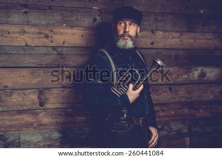 Half Body Shot of a Serious Middle Age Man in Black Attire with Cap Holding a Trumpet Instrument in front Wooden Wall While Looking to the Left of the Frame. - stock photo