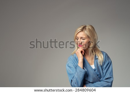 Half Body Shot of a Thoughtful Businesswoman in Blue Suit, Standing Against Gray Background with Hand Touching her Face and Looking Down, Emphasizing Copy Space. - stock photo