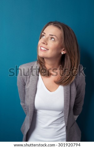 Half Body Shot of a Thoughtful Office Woman Looking Up with Happy Facial Expression Against Blue Green Wall Background. - stock photo