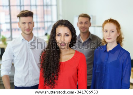 Half Body Shot of a Young Office Woman Against Three Co-workers Background, Looking at the Camera. - stock photo