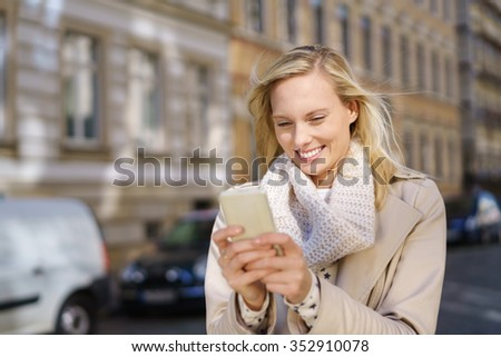 Half Body Shot of an Attractive Woman Chatting to Someone on Mobile Phone While Walking at the City Street. - stock photo