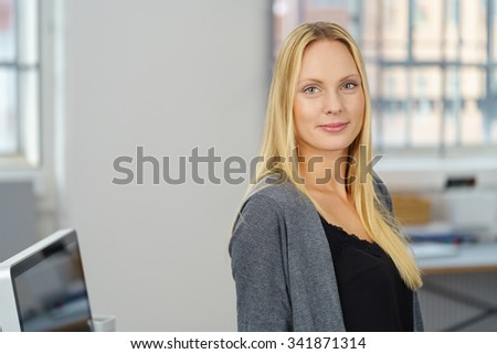 Half Body Shot of an Attractive Young Woman inside her Office, Smiling at the Camera. - stock photo
