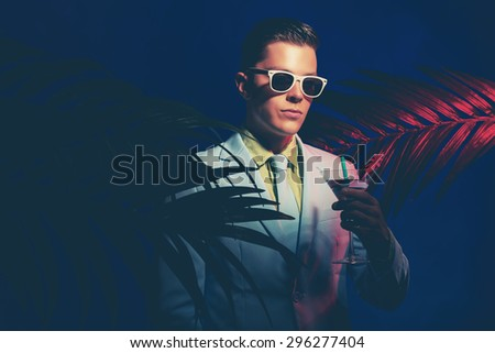 Half Body Shot of an Elegant Young Man Wearing Formal Suit and Sunglasses, Holding a Cocktail Drink Between Palm Leaves. - stock photo