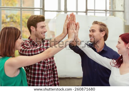 Half Body Shot of Conceptual Happy Young Friends Raising their Hands at the Middle - stock photo