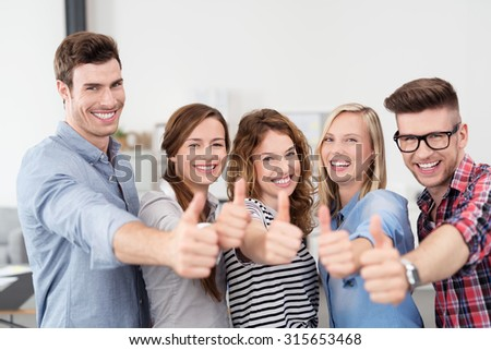 Half Body Shot of Five Happy Young Office Workers Showing Thumbs Up Hand Signs and Smiling at the Camera. - stock photo