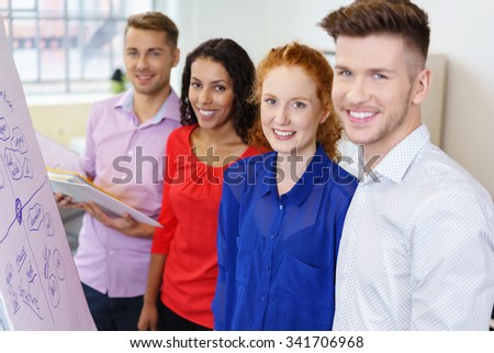 Half Body Shot of Four Young Business People Smiling at the Camera During Brainstorming Session In the Office. - stock photo