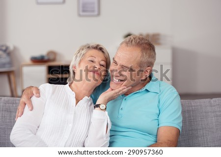 Half Body Shot of Sweet Middle Aged Couple Cuddling at the Gray Couch in the Living Room. - stock photo