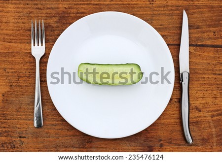 Half cucumber on plate with fork and knife.  Crash diet concept. - stock photo