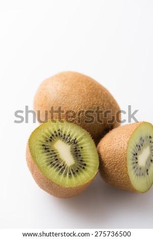 half cut, fresh and organic kiwi fruit isolated on white, close up, vertical - stock photo