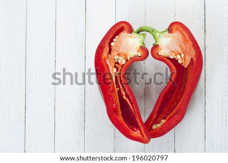 half cut red pepper on wooden, top view