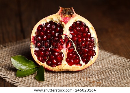 Half-cutted pomegranate on canvas with little green leaf - stock photo