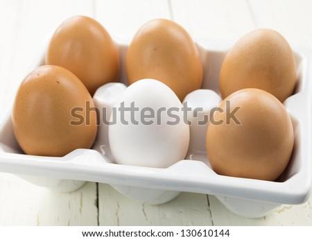 Half dozen brown eggs with one white in ceramic white container - stock photo